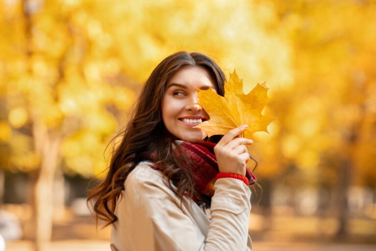 Pretty young woman smiling and covering her eye with yellow autumn leaf on walk at park