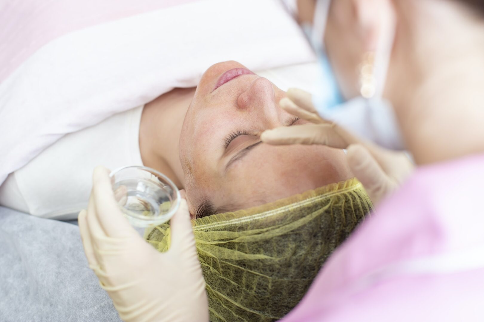 A professional cosmetologist applies a chemical peeling solution to the patient on the face
